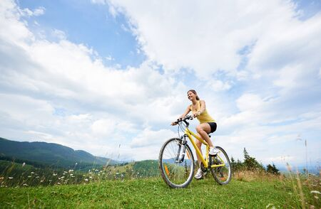 Young happy woman biker cycling on yellow mountain bicycle on a grassy hill, enjoying summer day in the mountains. Outdoor sport activity, lifestyle concept