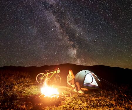 Young woman tourist having a rest at night camping near burning campfire, illuminated tourist tent, mountain bike under incredible beautiful evening sky full of stars and Milky way. Tourism concept Stockfoto