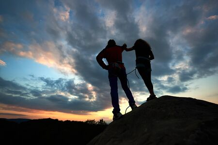Two climbers reaching summit one holding hand of his partner assisting to make last step to top. Teamwork couple helping hand trust help, silhouette success in mountains. Amazing heaven on background. Stock Photo