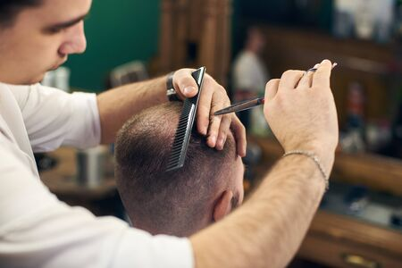 Skillful hairdressers hands cutting off male hair with professional tools in barbershop. Short haircut for men with scissors and comb helping. Masterful hands in workflow. Blurred background.