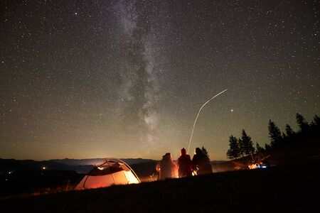 Night camping in the mountains. Back view of young friends hikers resting together around bonfire near tourist tent. On background forest and beautiful night starry sky full of stars and Milky way.