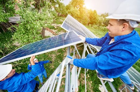 Team of three technicians mounting photo voltaic panel to stand-alone solar system platform on bright sunny day. Alternative energy, professionally done job and financial investment concept. 写真素材
