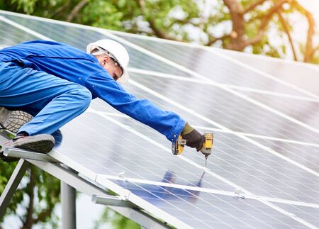 Young construction worker connects photo voltaic panel to solar system using screwdriver on sunny day. Alternative cheap sun energy production and profitable financial investment concept. Stock Photo