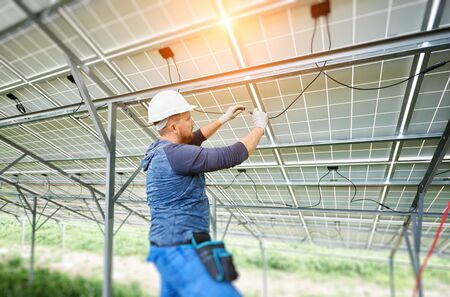 Young electrician connecting electrical cables inside the lit by sun solar modules. Installing and wiring of solar photo voltaic panel system. Alternative energy and profitable investment concept. Imagens