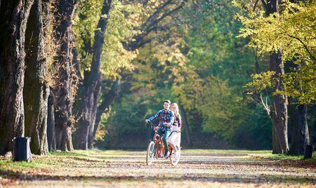 Jeune couple de touristes, bel homme barbu et jolie femme blonde aux cheveux longs faisant du vélo ensemble tandem double vélo rouge par ruelle ensoleillée avec des feuilles d'or sur fond de grands arbres à l'automne