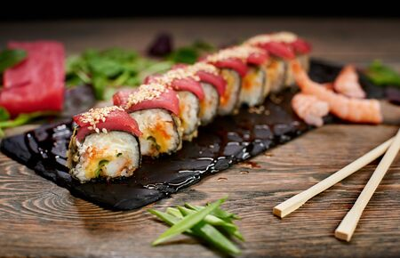 Sushi covered with tuna and sesame seeds on sloppy lubricate stone plate. Focus on details. Front view. Bamboo chopsticks, green onion on table. Tuna piece, shrimps, salad leaves on blurred background