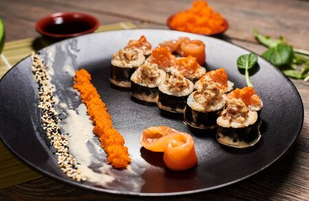 Appetizing hot sushi rolls in creamy sauce serving with salmon, caviar and sesame seeds in big black plate. Sauces and leaves on blurred background. Front detailed view. Exotic Japanese dish recipe.