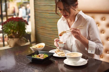 Brunette woman in white blouse with red lips ordering meal in luxury Japanese restaurant. Female eating four course lunch including soup, tempura shrimps, noodles and warm salad using food sticks. Stock Photo