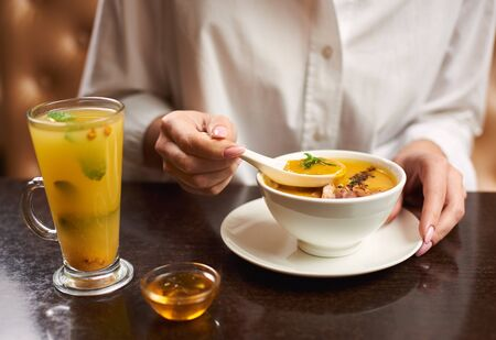 Crop of woman in white blouse holding in hands white bowl with orange cream soup. Female eating in restaurant first dish and tea with mint and honey near. Concept of healthy food. 版權商用圖片