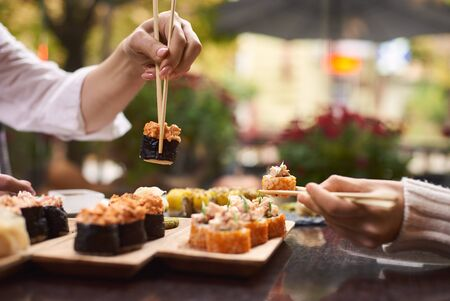 Two women sitting in asian restaurant and eating sushi set with help of chopsticks. Colleagues sharing tasty Japanese dinner with each other. Girls enjoying oriental meal from rice and seafood.