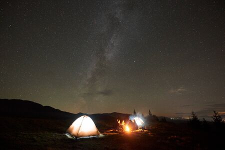 Night camping under stars. Group of five tourists, men and woman with guitar sitting by burning bonfire at tourist tents under dark sky with bright sparkling stars and Milky Way constellation.