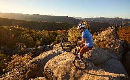 Courageous cyclist standing on back wheel on trial bike. Sportsman rider balancing on the edge of big boulder on the top of mountain at sunset. Concept of extreme sport active lifestyle Reklamní fotografie