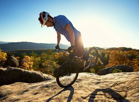 Professional cyclist standing on front wheel on trial bicycle. Athletic sportsman biker making acrobatic stunt on the edge of big boulder on the top of mountain at sunset. Concept of extreme sport