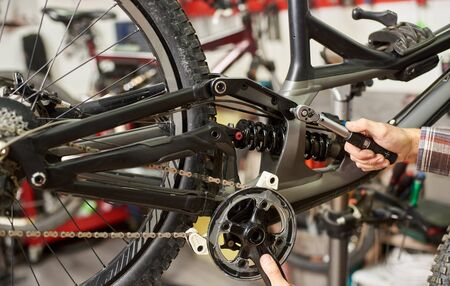 Cropped shot of male mechanic working in bicycle repair shop, cyclist repairing mountain bike using special tool Imagens