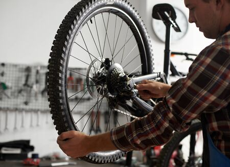 Cropped shot of male mechanic working in bicycle repair shop, repairman fixing bike using special tool, wearing protective workwear