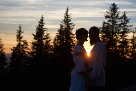 Silhouettes of young couple in love in the evening. Bearded man and happy woman touching noses, smiling and looking at each others words. Beautiful sunset, cloudy sky and forest on blurred background