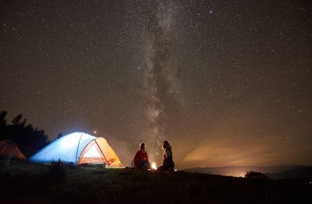 Night summer camping in the mountains. Romantic couple hikers having a rest together, sitting beside campfire and glowing tourist tent under beautiful night starry sky full of stars and Milky way.