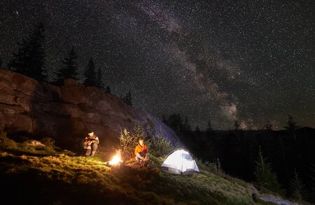 Night camping in the mountains. Happy couple travellers sitting together beside campfire and glowing tourist tent. On background big boulder, forest and night starry sky full of stars and Milky way. 版權商用圖片