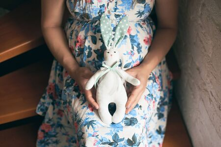 View from above of pregnant mother in flowery dress sitting on stairs, embracing belly and holding cute toy bunny for future child. Mother waiting for baby. Concept of anticipation. Фото со стока