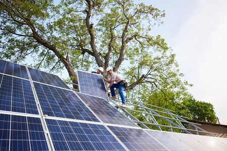 Two technicians mounting heavy solar photo voltaic panel on tall steel platform on green tree and blue sky background. Exterior solar panel voltaic system installation, dangerous job concept.
