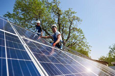 Dos técnicos sentados en una plataforma metálica instalando un panel fotovoltaico solar pesado sobre un cielo azul y un árbol verde de fondo. Instalación de sistema de panel solar independiente y concepto de profesionalismo. Foto de archivo