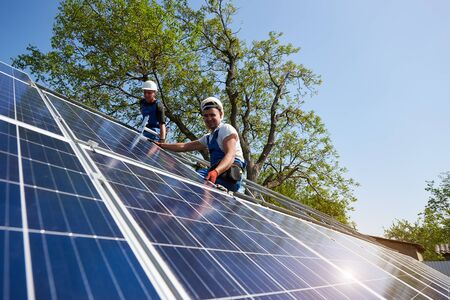 Two technicians sitting on metal platform installing heavy solar photo voltaic panel on blue sky and green tree background. Stand-alone solar panel system installation and professionalism concept. Foto de archivo