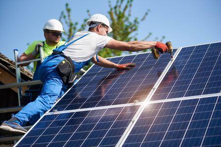 Dwóch pracowników techników instalujących ciężkie panele fotowoltaiczne na wysokiej stalowej platformie. Zewnętrzna instalacja solarna, alternatywna koncepcja wytwarzania zielonej energii odnawialnej.