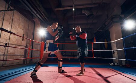 handsome male fighter training mma with his trainer in the ring at the health club