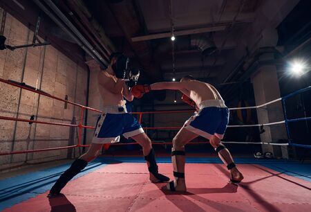 Two adult boxers practicing kickboxing in the ring at the sport club