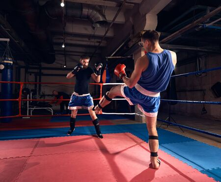 Two muscular sportsmen kickboxers practicing kickboxing in the ring at the sport club Banco de Imagens