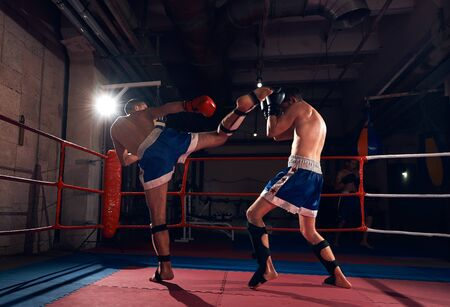 Two anger fighters exercising kickboxing in the ring at the health club