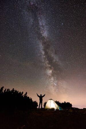 Silhouette of male hiker resting at night camping on the top of mountain beside glowing tourist tent. Man traveller holding hands lifting up, enjoying view of night sky full of stars and Milky way.