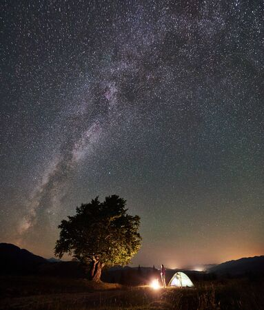 Female camper having a rest at summer camping in the mountains beside campfire, glowing tourist tent and big tree. Young woman enjoying view of night sky full of stars and Milky way. Astrophotography