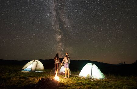 Active couple hikers resting at summer night camping in the mountains. Back view of man and woman standing beside campfire and glowing tourist tents under starry sky full of stars and Milky way.