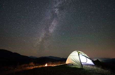 Tourist camping at night in the mountains. Illuminated tent and campfire under wonderful night sky full of stars and Milky way