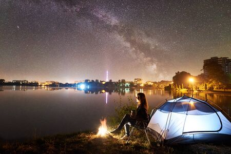 Night camping on lake shore near campfire. Woman with cup of coffee sitting on chair near tourist tent, enjoying evening sky full of stars and Milky way, quiet water surface, city lights on background