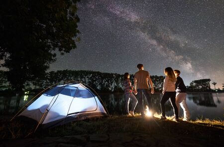 Night camping on lake shore near campfire. Two couple having a rest together near illuminated tent. Friends enjoying view of night sky full of stars and Milky way, quiet water surface on background. 版權商用圖片