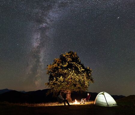 Romantic couple hikers enjoying summer night camping in mountains. Man and woman sitting on chairs beside bonfire, glowing tourist tent and big tree under starry sky full of stars and Milky way.