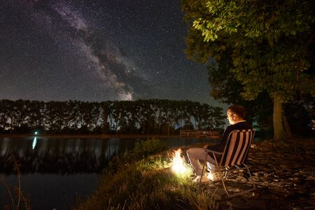 Male traveller having a rest on lake shore near bonfire, sitting on chair under big tree, enjoying beautiful view of night sky full of stars and Milky way, city lights on background. 版權商用圖片