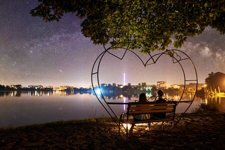 Back view of man and woman sitting on a bench near campfire on the shore near lake under tree. Couple enjoying amazing view of evening sky full of stars, quiet water surface, city lights on background 版權商用圖片