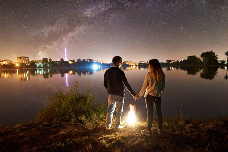 Back view of young family - man and woman standing on a lake shore near bonfire, holding hands, enjoying amazing view of night sky full of stars and Milky way above quiet water surface and city lights