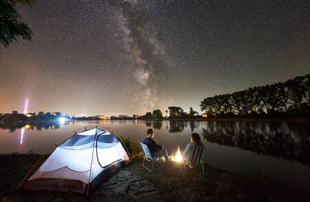 Night camping on lake shore. Back view of couple tourists sitting on chairs near campfire, glowing tent, enjoying beautiful view of evening sky full of stars and Milky way, city lights on background.