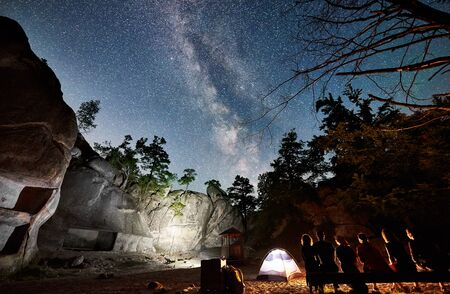 Back view of friends hikers having a rest together on a bench beside camp, campfire and illuminated tourist tent at night. On background night starry sky full of stars and Milky way, mountain rocks.
