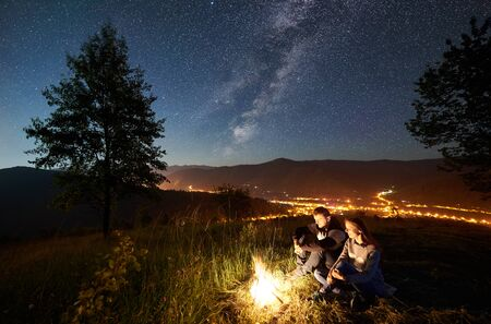 Young happy romantic couple tourists having a rest at campfire under amazing night sky full of stars and Milky way. On the background beautiful starry sky, mountains, big tree and luminous town