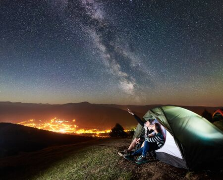 Young happy couple hikers having a rest at camp in illuminated tourist tent. Man pointing at amazing night sky full of stars and Milky way. On the background starry sky, mountains and luminous town 版權商用圖片