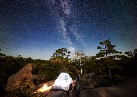 Woman hiker relaxing on rocky mountain top beside camp, bonfire and tourist illuminated tent, enjoying view of night sky full of stars and Milky way. On background starry sky, big boulders and trees 版權商用圖片