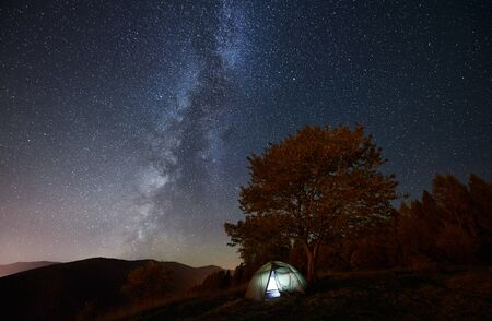 Tourist camping near forest at summer night. Illuminated tent under amazing night sky full of stars and Milky way. On the background beautiful starry sky and mountains
