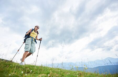 Low angle view of attractive woman hiker hiking mountain trail, walking on grassy hill, wearing backpack and sunglasses, using trekking sticks, enjoying summer day. Outdoor activity, lifestyle concept