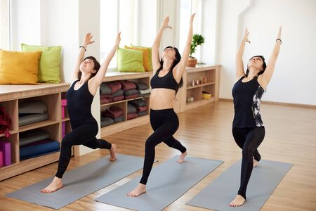 Fit adult women practicing yoga poses in fitness class. Group of healthy strong female doing fit exercises in white gym. Health care and lifestyle. Yoga masters demonstrate High lunge and Warrior pose Reklamní fotografie