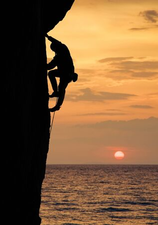 Silhouette of male climber ascenting high up on straight cliff at sunset. Side view. Dangerous and risky rock climbing above ocean. Big round sun on beautiful orange sky on background. Copy space Reklamní fotografie